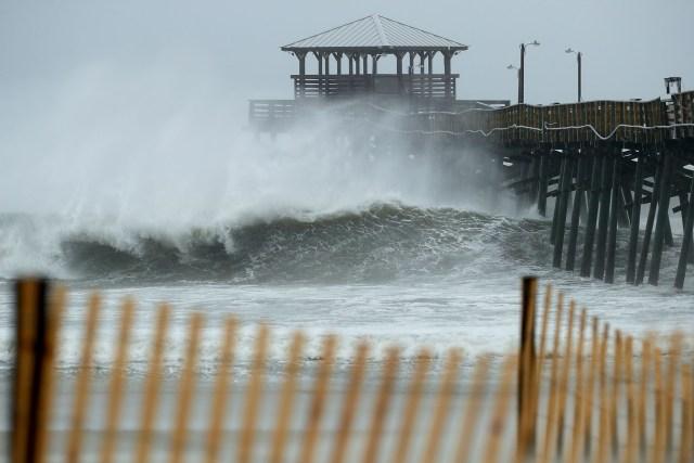 Las olas se estrellan debajo del muelle de Oceana Piers, en playa Atlanti, Carolína del Norte (AFP)