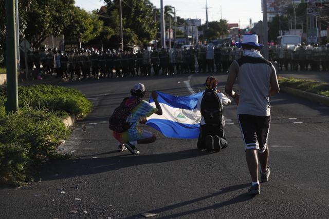 """Policías montan guardia mientras manifestantes opositores participan en la Marcha de los Sombreros para pedir la libertad de los """"presos políticos"""". (EFE/Jorge Torres)"""