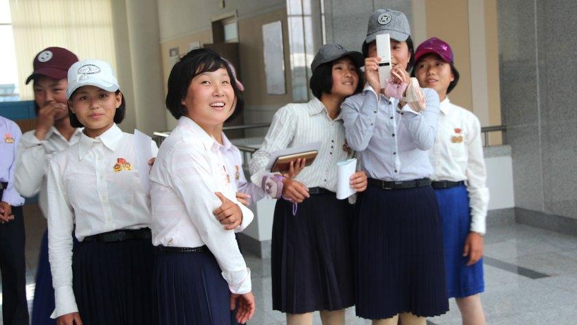 Estudiantes de secundario de Pyongyang, identificadas con prendedores oficiales, toman fotos a los extranjeros con un teléfono celular. (Foto: Florencia Grieco – @flowergrieco)