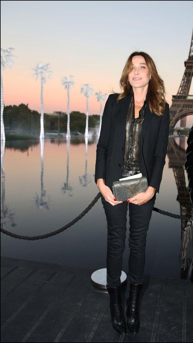 Carla Bruni, con blusa y clutch metalizado.
