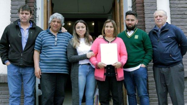 Adriana, hermana del soldado Mario Gustavo Rodríguez, muestra el informe de la Secretaría de Derechos Humanos con la identificación