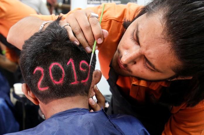 Un peluquero trabaja sobre la cabeza de su cliente en una barbería de Ahmedabad, India