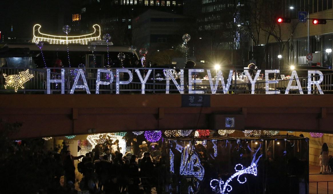 La gente camina entre decoraciones iluminadas en la calle Cheonggye durante las celebraciones de Año Nuevo en Seúl, Corea del Sur