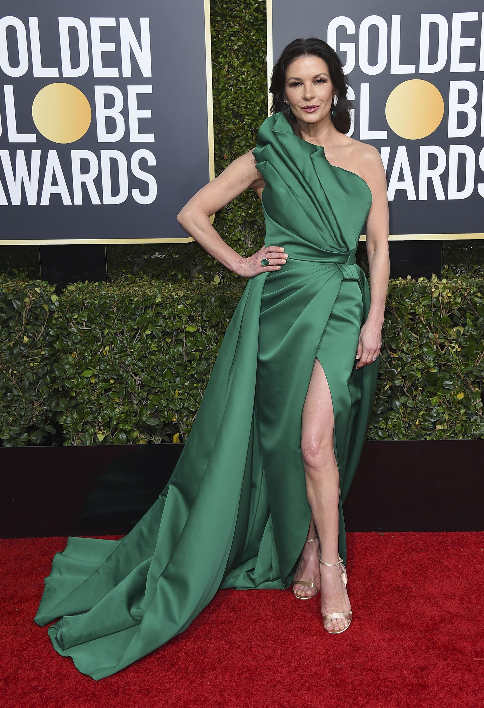Catherine Zeta-Jones vistió de verde con sandalias doradas. El diseño de corte asimétrico con drapeado en la cintura y gran tajo en la falda. Completó el look con un delicado anillo de esmeraldas y aros gota de brillantes