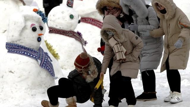 Niños juegan en la nieve con sus trineos en Harbin
