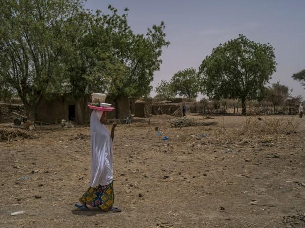 Zeinoura Mahissou, quien huyó de un matrimonio forzado,carga tartas para vender en el mercado de Inkouregaou, en Niger (Laura Boushnak/The New York Times)