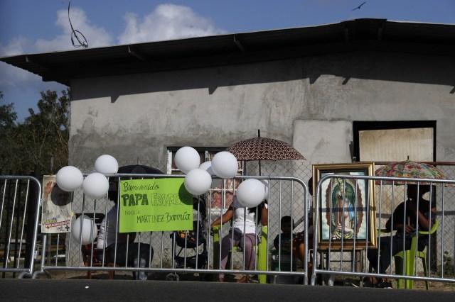 Los residentes esperan su momento mientras esperan que el Papa Francisco pasee en su móvil en el camino al centro de detención de menores en Las Garzas de Pacora, en Panamá, el viernes 25 de enero de 2019.