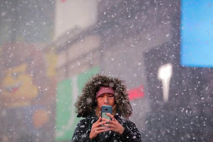 Otra mujer toma fotos en Times Square, en medio del frío y la nieve.