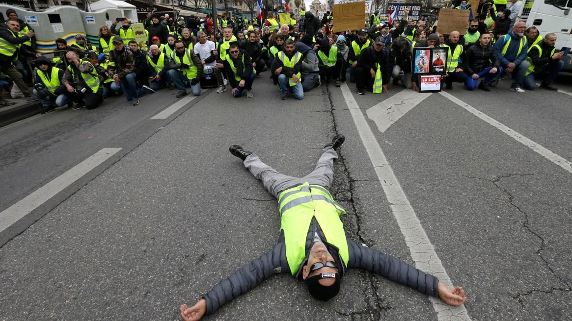 Una persona tendida sobre la calle(AP Photo/Claude Paris)