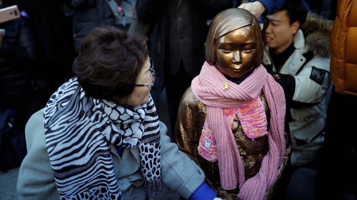 Lee Yong-soo, otra de las mujeres que fueron esclavizadas, al lado de una estatua que simboliza su lucha (REUTERS/Kim Hong-Ji)