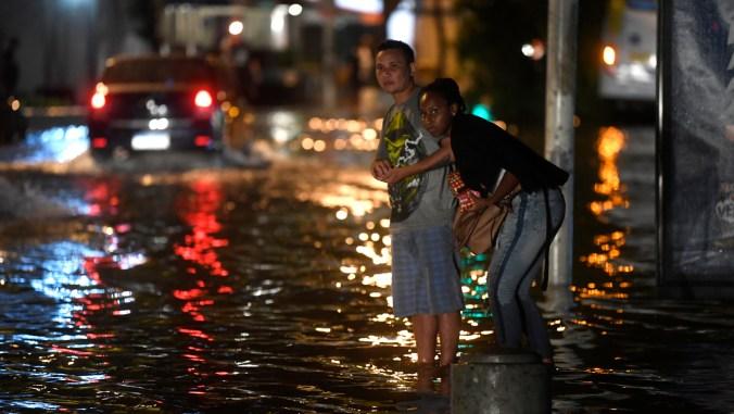 Una mujer y hombre intentan cruzar una calle inundada en Río de Janeiro. (AFP)
