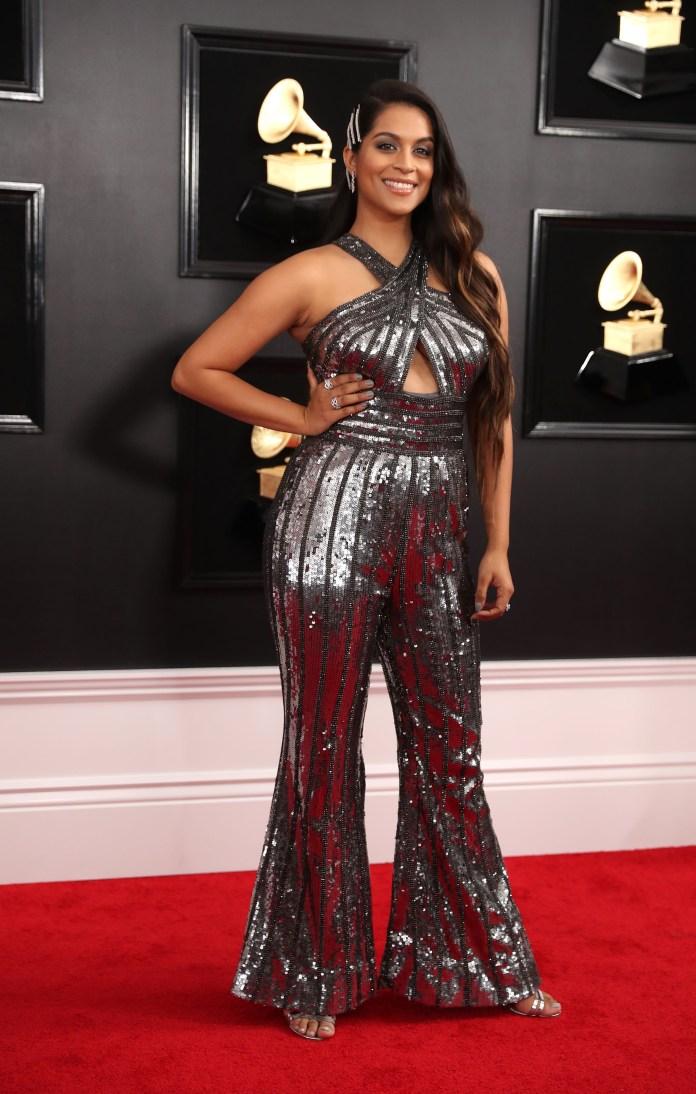 Lilly Singh asistió a los Grammy 2019 con un mono de pailletes plateados y grises. El diseño de cuello halter sin mangas. Lo completó con sandalias plateadas y mini anillos