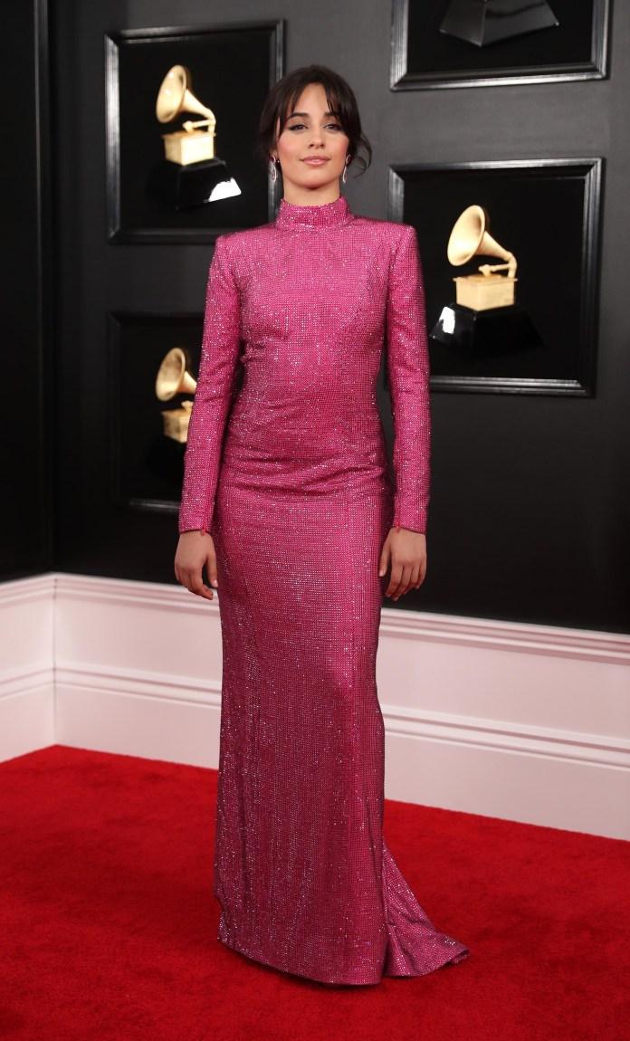 Camila Cabello inaguró la red carpet de los Grammy con un vestido sirena en color fucsia de mangas largas y cuello polera. Lo completó con aros joya en forma de hoja con piedras preciosas