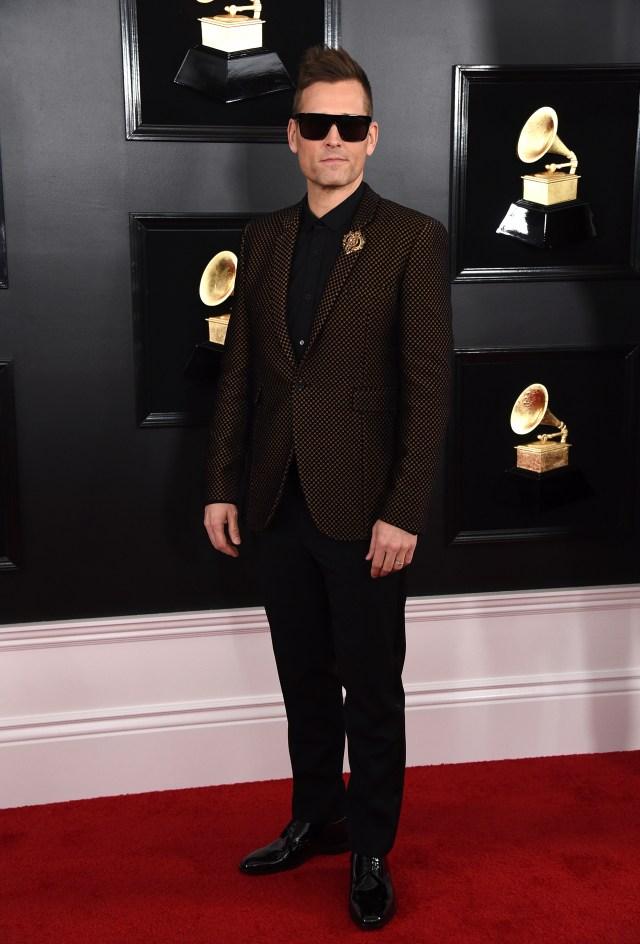 Kaskade apostó a un esmoquin negro con camisa, pantalón y zapatos acharolados negros. El distintivo fashionista, el saco cuadrillé dorado y prendedor. Completó el look con gafas de sol oscuras