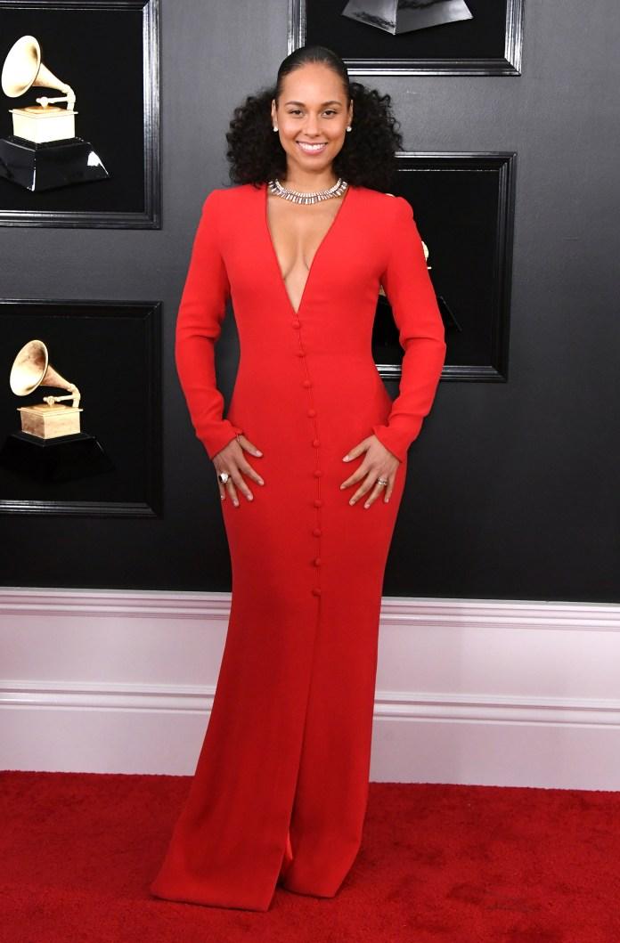 Total red .Alicia Keys lució un vestido sirena abotonado de mangas largas y escote V. Completó el look con gargantilla, anillos y pequeños aros de brillantes