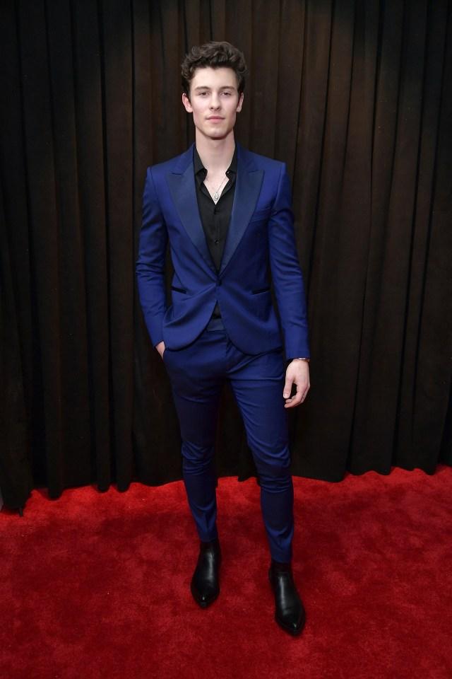 Shawn Mendes asistió a la ceremonia de los premios Grammy con un esmoquin achupinado en azul francia con camisa negra. Completó el look con botas de cuero en punta