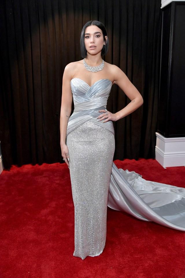 Dua Lipa llegó a la red carpet de los Grammy con un vestido plateado de lúrex y seda drapeada. Completó el look con anillos y gargantilla de brillantes