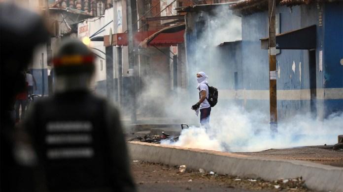 Un activista venezolano observa mientras se enfrenta a las fuerzas de seguridad en Ureña, Venezuela (Reuters)
