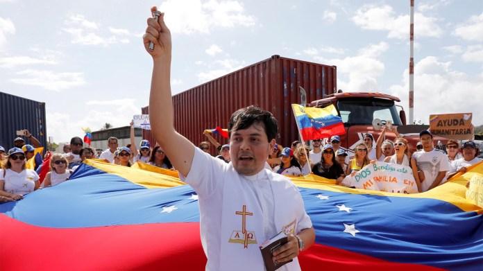 Un sacerdote reza junto a los partidarios del líder de la oposición de Venezuela, Juan Guaidó, con banderas y letreros que respaldan la ayuda humanitaria en el puerto de Willemstad en la isla de Curazao (Reuters)
