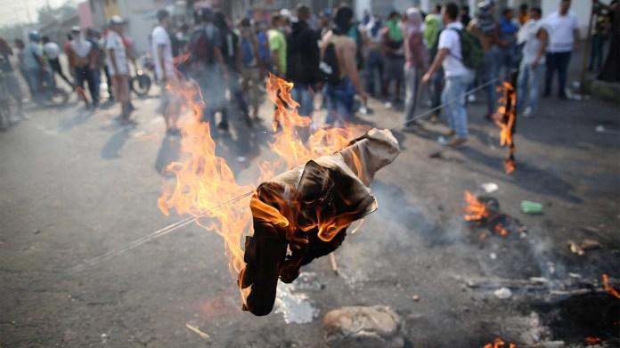 Los manifestantes queman la ropa de la milicia de un hombre venezolano mientras se enfrentan con las fuerzas de seguridad en Ureña (Reuters)
