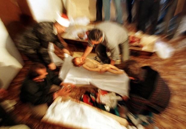 Un hombre albano coloca el cuerpo de Mozzlum Sylmetaj, de 2 años, en un ataúd cerca a los cuerpos de otros familiares asesinados por tropas yugoslavas en su cruce por Kosovo, en octubre de 1998