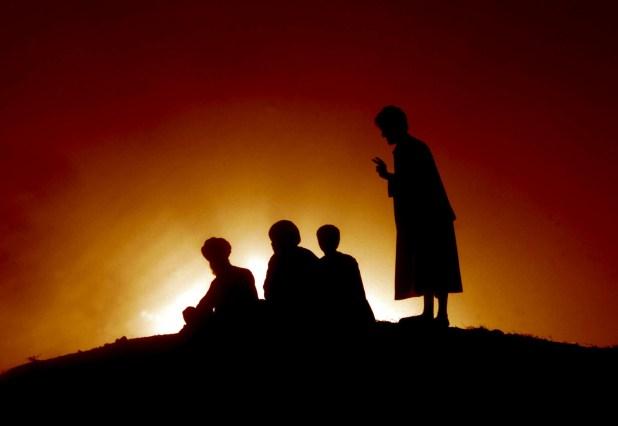 Miembros de una comunidad afgana descansan en una ladera desde la que observan el movimiento de tropas de la OTAN, en noviembre de 2001