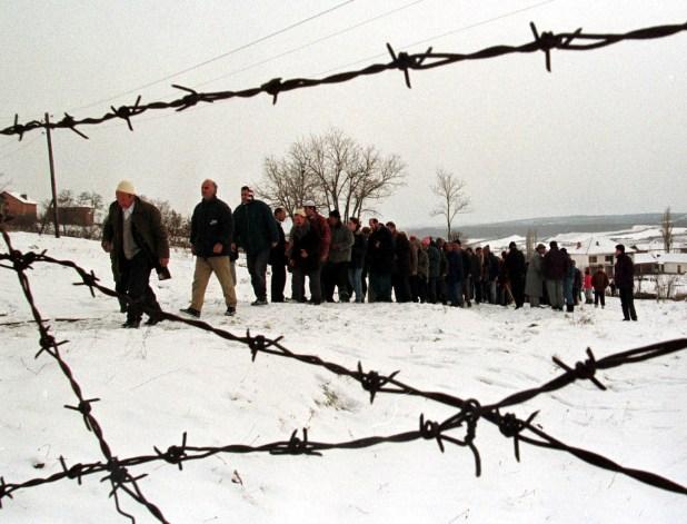 Una comunidad de Albania forma una fila para honrar a la familia de dos víctimas de la violencia étnica en Kosovo, en enero de 1999