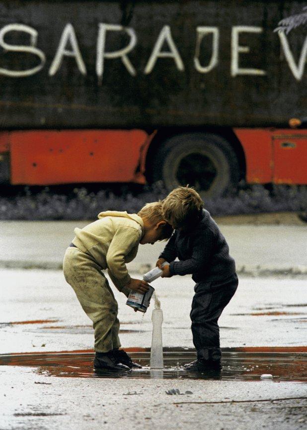 Niños bosnios tratan de juntar agua de lluvia en un charco de Sarajevo, en agosto de 1993