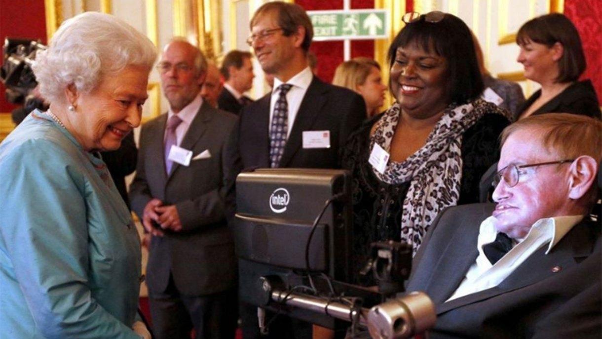 Stephen Hawking junto a su enfermera Patrica Dowdy, en una recepción que le brindó la reina Isabel en el Palacio de Buckingham