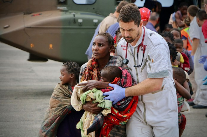 El 19 de marzo de 2019, el personal de asistencia humanitaria escoltó a las personas a la seguridad en el aeropuerto de la ciudad costera de Beira, en el centro de Mozambique, después de que el área fuera afectada por el ciclón Idai. (Photo by ADRIEN BARBIER / AFP)