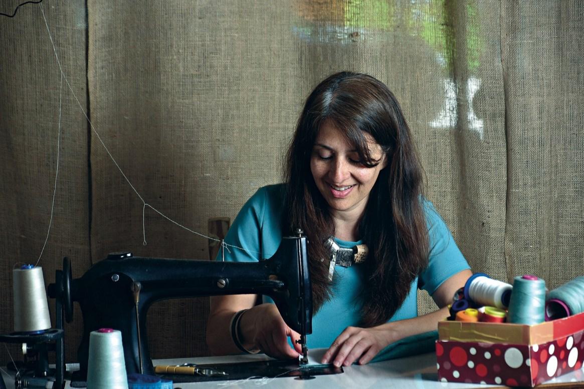 Mercedes sentada en la máquina de coser, su compañera durante largas horas.