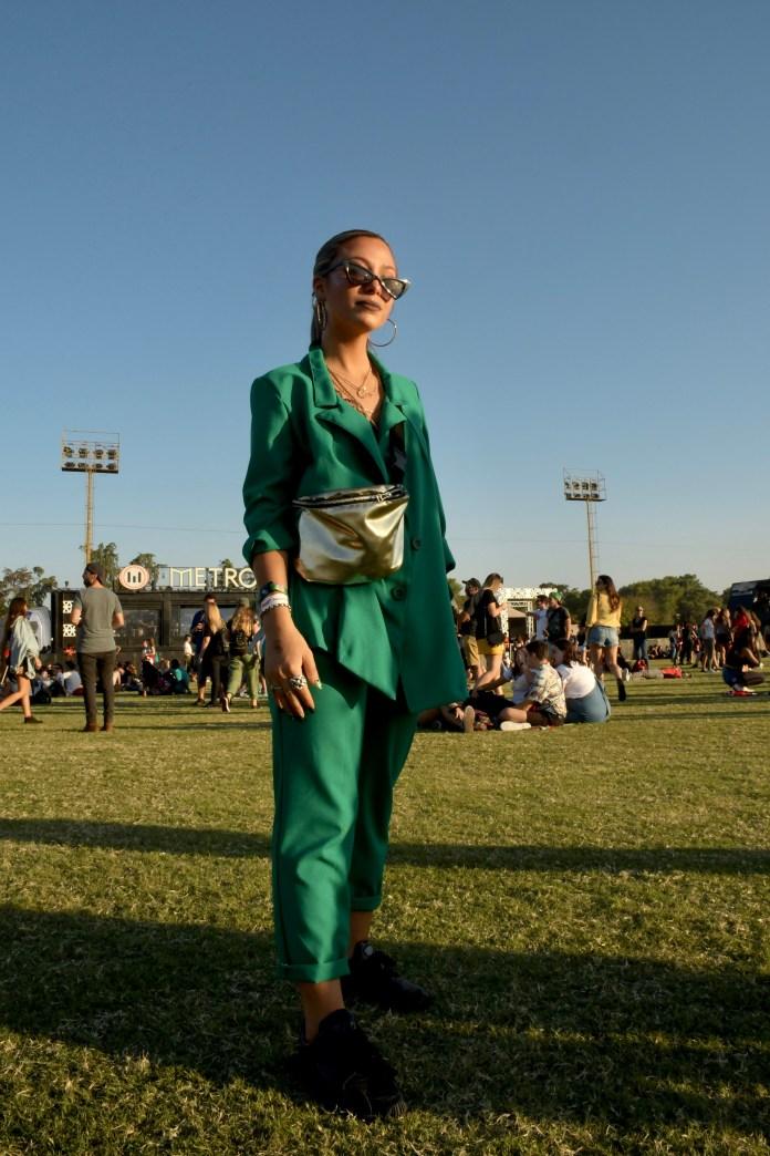 El look sastrero también estuvo presente en el Lolla. El traje oversized de saco irregular en color verde esmeralda, con el toque fashionista, la riñonera. No pueden faltar los mini anteojos de sol y como accesorio, las maxi argollas