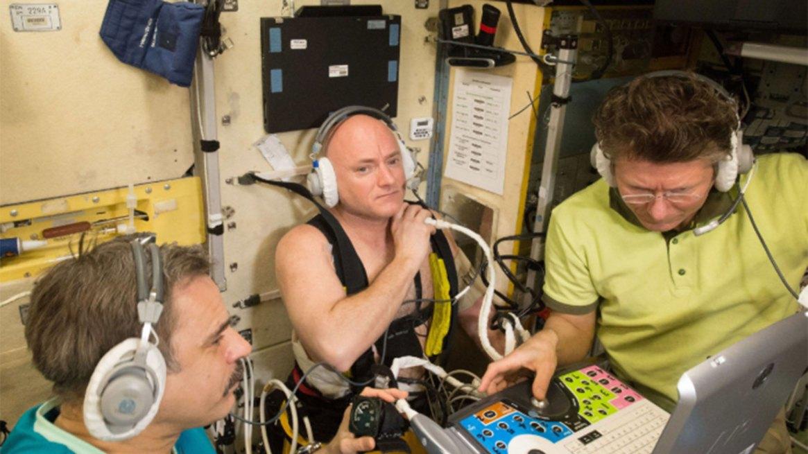 Scott Kelly (centro) utiliza un dispositivo Chibis de presión negativa en la parte inferior del cuerpo, mientras que los cosmonautas rusos ayudan a monitorear y medir médicamente sus fluidos corporales mientras están en órbita terrestre en 2015.
