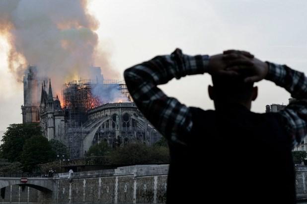 Un hombre observa arder la histórica catedral de Notre Dame, envuelta en llamas, en el centro de París el 15 de abril de 2019. (AFP)