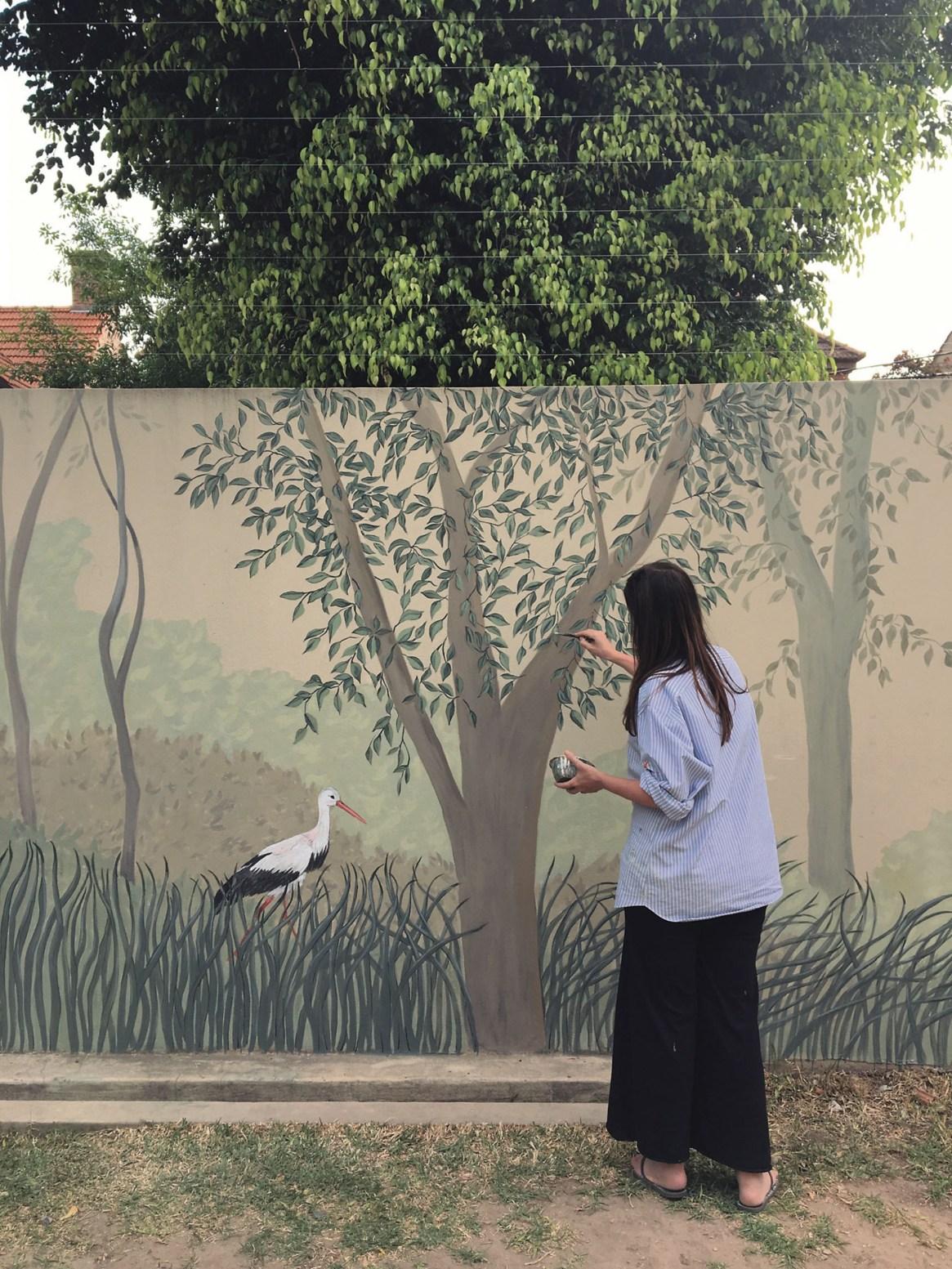 Un mural con que sigue la figura de un árbol y le suma garzas, pintado en un patio interno de un PH en Recoleta.