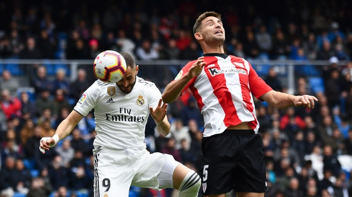Real Madrid's French forward Karim Benzema (L) scores a header past Athletic Bilbao's Spanish defender Yeray Alvarez during the Spanish League football match between Real Madrid and Athletic Bilbao at the Santiago Bernabeu Stadium in Madrid on April 21, 2019. (Photo by GABRIEL BOUYS / AFP)