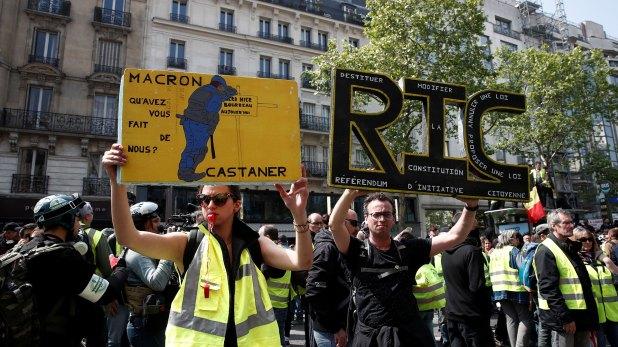 """Los chalecos amarillos asisten a una manifestación durante el tradicional día del trabajo del Primero de Mayo en París, Francia, el 1 de mayo de 2019. La pancarta dice: """"RIC (Referéndum Iniciado por los Ciudadanos)"""" (Reuters)"""