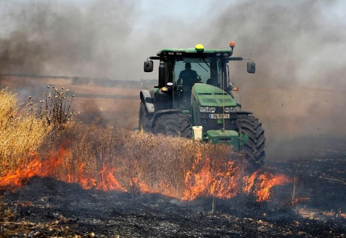 Un agricultor israelí maneja su tractor en medio de un incendio causado por protestantes palestinos. (Menahem KAHANA / AFP)
