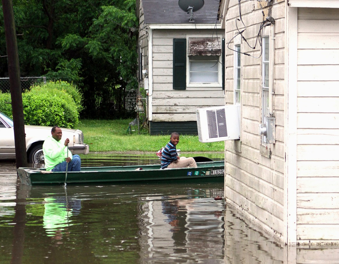Clarance Ferguson, a la izquierda, y su nieto Demarious Ferguson navegan en su barco por la larga calle Hugh en el sur de Greenville, Misisipi, el jueves 9 de mayo de 2019. (AP)