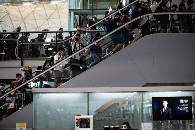 Los manifestantes cantan consignas mientrassuben por las escaleras mecánicas del aeropuerto(Foto de Philip FONG / AFP)