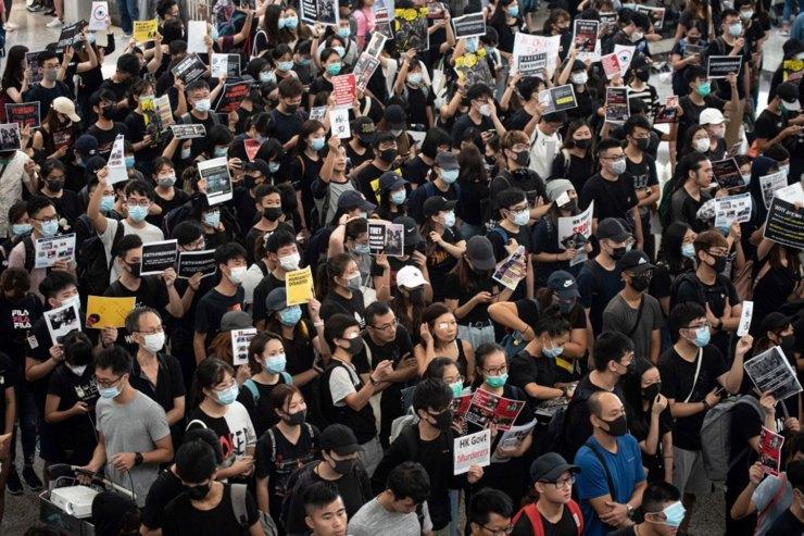 Los participantes intentan ocupar la sala de embarque durante la protesta (Foto de Philip FONG / AFP)