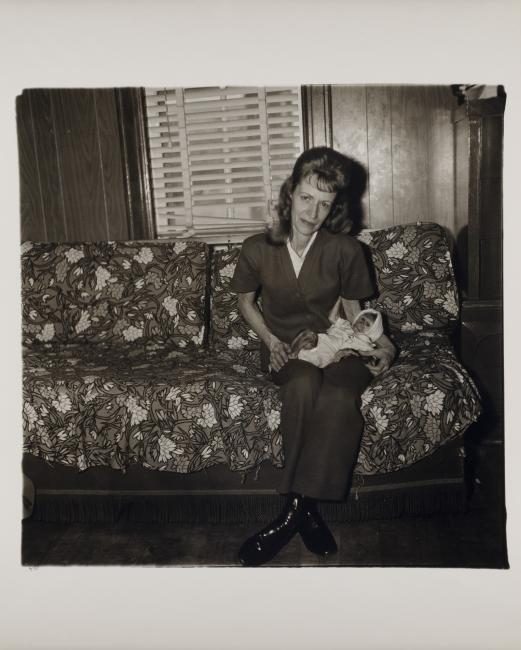 "A black and white photograph by Diane Arbus titled ""Mrs. Gladys 'Mitzi' Ulrich with the baby, Sam, a stump-tailed macaque monkey"""