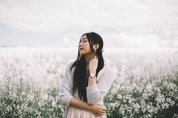 Woman in a field of flowers, allergy-free. Natural allergies treatment home remedies can work.