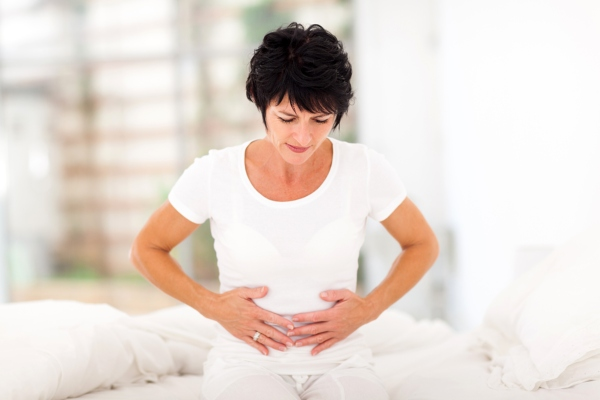 Woman with stomach problems. IBS diet, IBS causes, IBS symptoms.