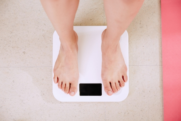 Woman on a scale, belly fat loss diet, belly fat loss home remedies.