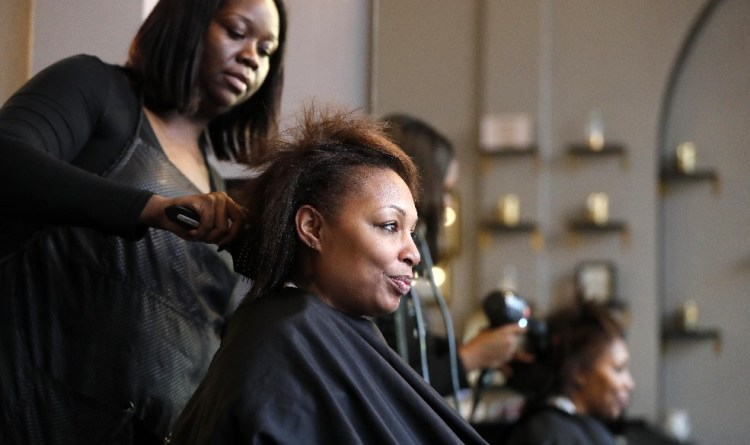 Human-trafficking survivor Mahogany Bell gets a makeover from stylist Breunte Jemes at High Klass Hair on Allen Street before Friday night's benefit to raise funds for a 'safe house' in Buffalo. (Mark Mulville/Buffalo News)