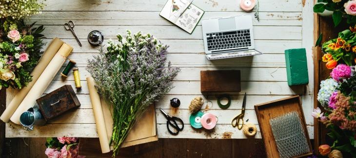 desk with scissors, laptop, flowers