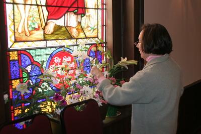 Altar Guild member arranging Easter flowers in window