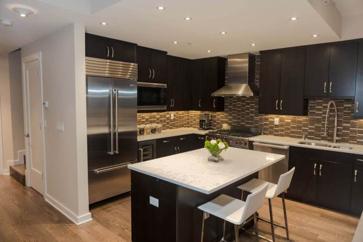 Black Wood Cabinetry And Island Contrast With Patterned Tile Backsplash White Marble Countertops