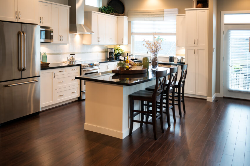 In this sleekly modern kitchen with an open floor plan, a white island with black countertop stands at center. The rich hardwood flooring warms the look, contrasting with white cabinetry.